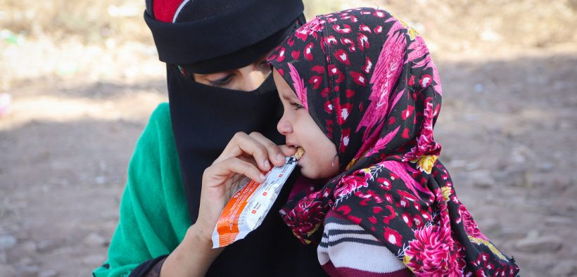 WFP/Saleh Bin Haiyan A mother feeds her daughter a nutrition bar she received from a mobile health clinic in Yemen.