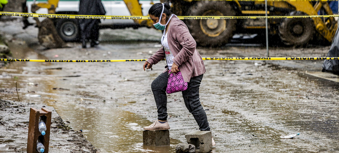 A woman walks across a flooded road in Santo Tomás, San Salvador, after Tropical Storm Amanda caused a landslide.